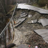 Stor vägskada intill ett vattendrag. Stor del av vägen är urgröpt.