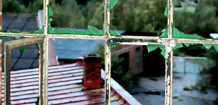 Utsikt över grönt landskap genom en trasigt fönster i gammal industrimiljö