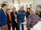 Sju personer (tre män och fyra kvinnor) står i grupp kring en metallskål på ett bord i laboratoriemiljö. En man har ryggen mot kameran.