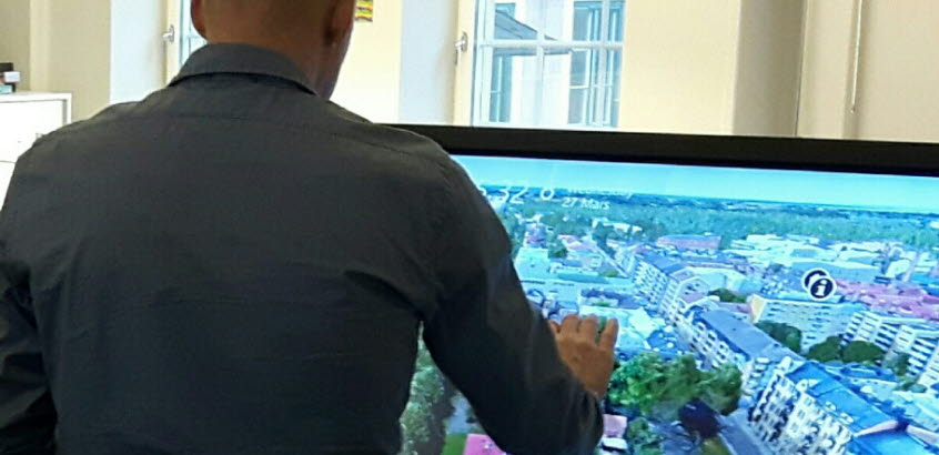 Man står vänd mot digital skärm som visar visualisering av hus och gator i stadsmiljö.