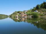 Göta älv fotat från vattnet där omgivningen och bebyggelse speglas i vattnet.
