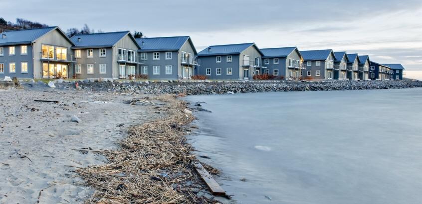 Flera hus på rad, byggda intill kusten.