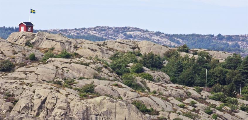 Liten röd stuga på toppen av en klippa.