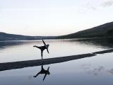 En person balanserar på ett ben, stående på en sten med armarna utsträckta, omgiven av vatten med fjäll i bakgrunden i skymningsljus