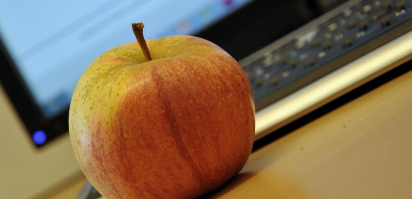 Ett äpple som ligger framför ett tangentbord.
