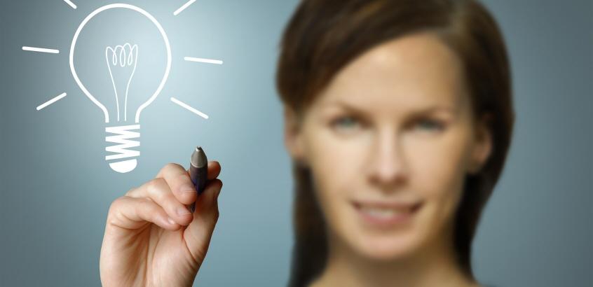 Kvinna som ritat en glödlampa framför sig. Ska illustrerar idéer som föds.