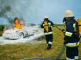 Två brandmän som sprutar skum på en brinnande bil.