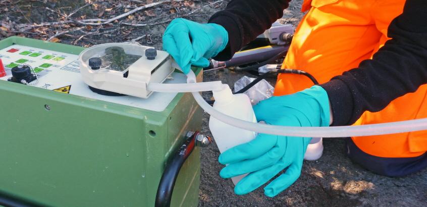 Provtagning av grundvatten. Händer som håller en vit plastflaska mot ett rör  från provtagningsutrustningen.