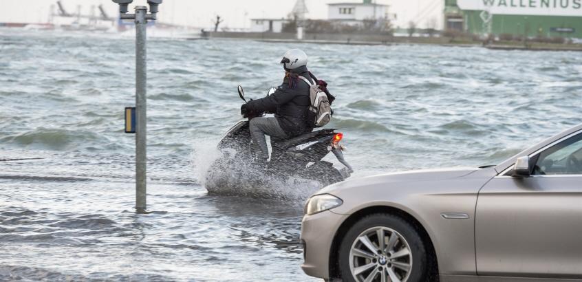 En bil och en moped som kör på en översvämmad väg.