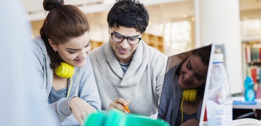 Två studenter, en tjej och kille, som arbetar i biblioteksmiljö