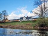 Hus som är byggda i sluttningen ner mot Norsälven. Fotot är tagit utifrån vatten och in mot land.