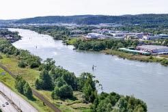 Flygfoto över del av Göta älv med motorväg och järnvägsspår till vänster om älven.