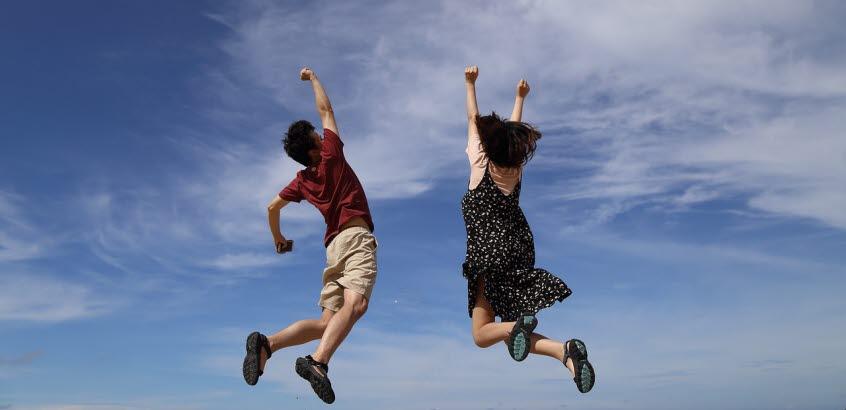 En man och en kvinna hoppar upp mot en himmel.