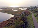 Bild ovanifrån med vy över hav, strandängar och till höger en lång bro.