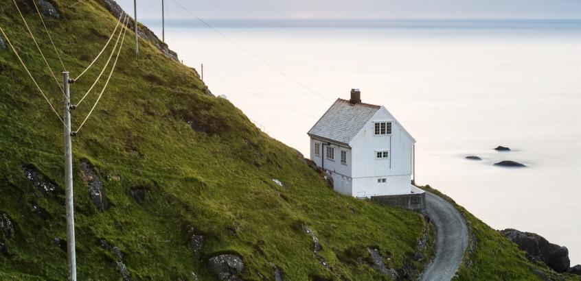 Ett ensamt hus byggt i en bergsslänt ner mot vatten.