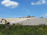 Arbetsfordon och grävmaskiner som täcker över en deponi.