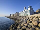 Lägenhetskomplex byggt intill vatten. Stenblock vid strandkanten skyddar mot vågor.