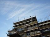 Överdel av hus som håller på att byggas. Foto taget från marken och upp mot himlen.